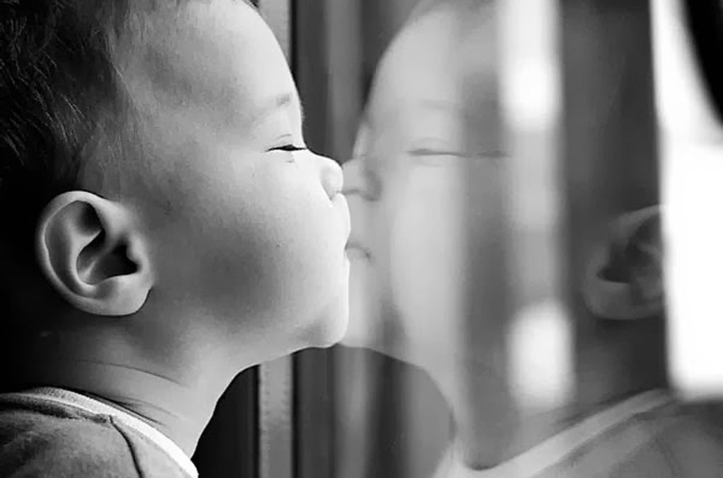 A toddler kissing his reflection in the glass